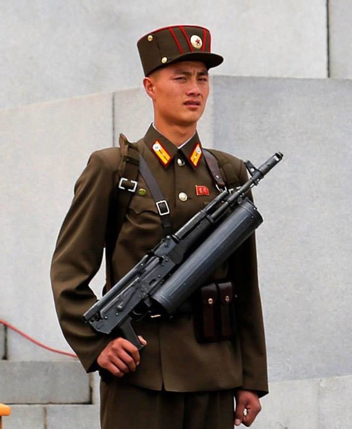 admin's bodyguards. Apparently, these North Korean Type 88 AK-74 clones have been modified with a top folding stock to accommodate the helical magazine that the